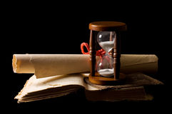 Hourglasses and book On black. A background Stock Photo
