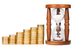 Hourglasses and coin time and money concept Stock Image