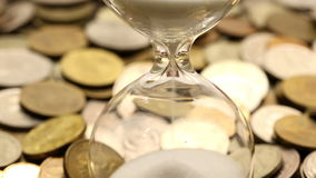 Hourglasses and coins stock footage