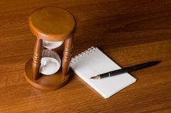 Hourglasses and Notebook. On a wooden table Royalty Free Stock Photography