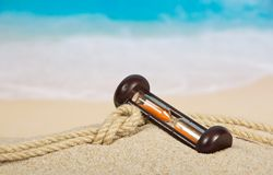 Hourglasses and rope on the sandy coast Royalty Free Stock Photography