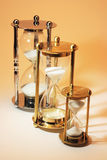 Hourglasses. Row of Hourglasses on Warm Background Stock Photo