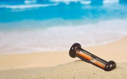 Hourglasses on a sandy beach. Wooden hourglasses on a sandy beach background Stock Image