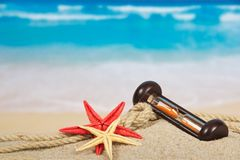 Hourglasses, starfishes on the sea coast Stock Image