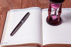 Hourglasses und Buch auf einer hölzernen Tabelle Stockfoto