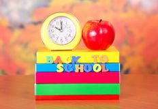 Hours and apples on a stack of books Royalty Free Stock Photos