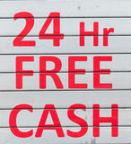 24 hours free cash - Message written in red. On grey shop shutters Royalty Free Stock Image