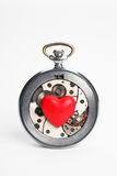 Hours and heart. Red heart and the mechanism of a pocket watch on a white background Stock Images