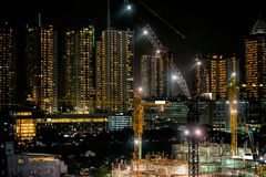24 hours non stop construction site at night. Ground breaking construction of MRT. Or Mass Rapid Transit Station with lots of tower crane stock images