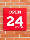 24 Hours Red Signboard. 24 Hours Red Signboard On Brick Background Stock Photo