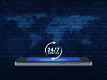 24 hours service icon on modern smart phone screen over map and. Computer binary code blue background, Full time service concept, Elements of this image Royalty Free Stock Images