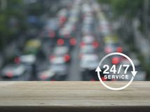 Full time service concept. 24 hours service icon on wooden table over blur of rush hour with cars and road, Full time service concept Stock Photo