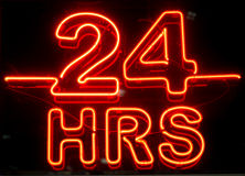 24 Hours Sign. A closeup to a bright neon 24 hours sign at night royalty free stock photos