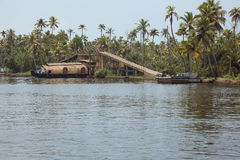 Housboat passing under a bridge. Over a canal in Alappuzha Stock Photo