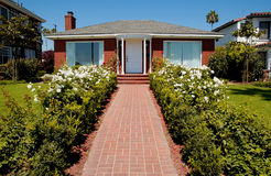 House. A red brick house with side walk stock photos