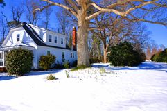 House. A country side house covered with snow with blue sky and oak tree in front yard Royalty Free Stock Photos
