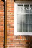 House. Detail (exterior). White window, red bricks and copper pipe Stock Images