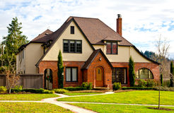 House. Peaceful house with green lawn and paved sidewalks stock image
