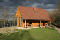 House. Traditional small wooden house near the river and stormy sky Stock Photos