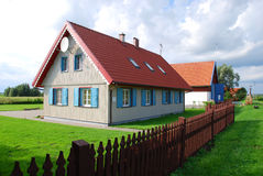 House. A well-kept family house with a wooden fence and a yard. Rural landscape view, small village Minge, Lithuania Royalty Free Stock Image