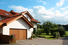 House. Beautiful house in Germany with blue sky and clouds. Surrounded by vegetation stock images