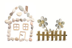 A house. With easy flower behind the fence made from little color pebbles Royalty Free Stock Image