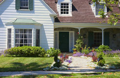 House. White house with flowered walkway and green grass royalty free stock photography