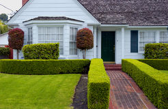 House. White house with red brick walkway and green grass Stock Image