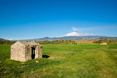 House abandoned in green field and volcano Etna Royalty Free Stock Images