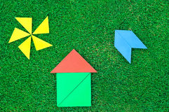 House, aircraft and sun made of tangram figures on natural grass Royalty Free Stock Photo