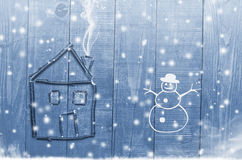 House arranged from twigs on wooden winter snowy blue background. Snowman Stock Photo