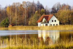 House ashore fores lake. Rural landscape - house under a red roof ashore forest lake royalty free stock photo