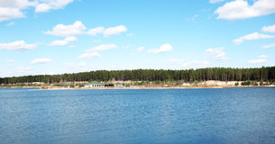 House ashore lake. Blue water and blue sky, forest at back of house Stock Photo