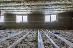 House attic under construction. Mansard walls and ceiling insulation with rock wool. Fiberglass insulation material in wooden fram. E for cold barrier stock photo