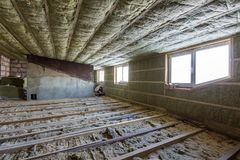 House attic under construction. Mansard walls and ceiling insulation with rock wool. Fiberglass insulation material in wooden fram. E for cold barrier stock photos