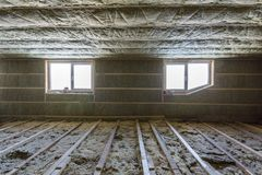 House attic under construction. Mansard walls and ceiling insulation with rock wool. Fiberglass insulation material in wooden fram. E for cold barrier royalty free stock image