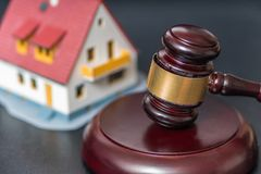 House auction concept. Gavel in front of a house model Stock Images