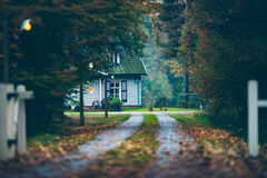 House in autumn forest with driveway at dusk. Royalty Free Stock Photo