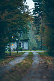 House in autumn forest with driveway at dusk. Royalty Free Stock Images