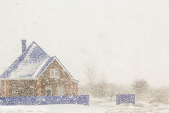 House on the background of plentiful snowfall Stock Photo