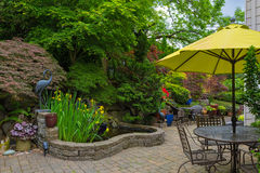 House Backyard Hardscape with Garden Patio Furniture. Home backyard hardscape and lush plants landscaping with garden furniture on paver brick patio spring Royalty Free Stock Photos