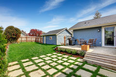 House backyard with patio area on walkout deck. House with fenched backyard. View of wooden walkout deck with small patio area royalty free stock photography