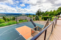 House backyard with sport court and patio area. View from walkout deck. House with sport court and patio area. Panoramic view from house walkout deck stock photography