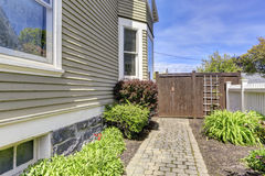 House backyard view. Walkway with bushes alongside Royalty Free Stock Photos