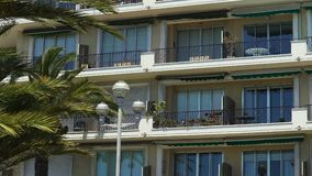 House balconies with awnings swaying in wind, real estate in sunny resort city stock video footage