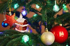 House, balls, stars and lighting garland on Christmas tree Royalty Free Stock Photography