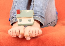 House on base from bare feet. Of a little girl - child sitting on sofa with orange cover Stock Photography