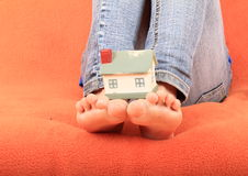 House on base from bare feet. Of a little girl - child sitting on sofa with orange cover royalty free stock photos