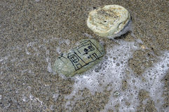 House on the beach. Child painted stone in the water having waves coming in royalty free stock photo