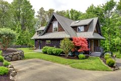 House with beautiful curb appeal. Clapbord siding brown house with green lawn and amazing blooming trees. View from the driveway Stock Images